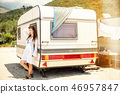 Beautiful young woman outside the camper van on a summer day 46957847