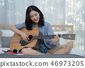Young Asian woman playing guitar in her bedroom. 46973205