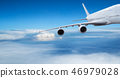 Huge two-storey passengers commercial airplane flying above dramatic clouds. 46979028