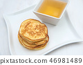 Pancakes and honey. In white porcelain plates 46981489