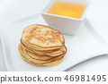 Pancakes and honey. In white porcelain plates 46981495
