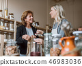 A female shop assistant serving a senior customer in a zero-waste shop. 46983036