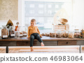 A barefoot small toddler boy sitting on a table in zero waste shop. 46983064