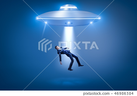 A businessman pulled toward an open hatch of a UFO by some invisible force. 46986384