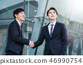 confident businessmen shaking hands and smiling 46990754