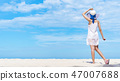 Beautiful woman walking on the beach with blue sky 47007688