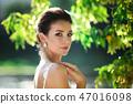 fashion photo of beautiful woman with dark hair in luxurious wedding dress posing outdoor. 47016098