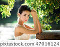 fashion photo of beautiful woman with dark hair in luxurious wedding dress posing outdoor. 47016124