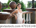 fashion photo of beautiful woman with dark hair in luxurious wedding dress posing outdoor. 47016148
