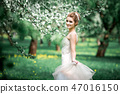 Portrait of young woman in the flowered garden in the spring time. 47016150