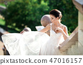 fashion photo of beautiful woman with dark hair in luxurious wedding dress posing outdoor. 47016157
