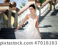 fashion photo of beautiful woman with dark hair in luxurious wedding dress posing outdoor. 47016163