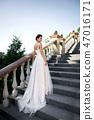 fashion photo of beautiful woman in wedding dress posing outdoor. 47016171