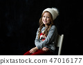Pretty girl stands on the black background of a chalkboard and smile 47016177