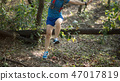 Woman trail runner running in forest 47017819