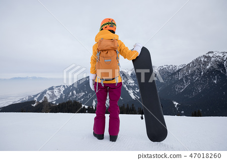 snowboarder with snowboard on winter mountain top 47018260