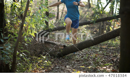 Sportswoman cross country trail running in forest 47018384