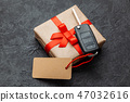 Gift box with car keys with remote control alarm system with red ribbon bow and label. 47032616