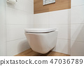 White toilet on the wall with sloseed lid. 47036789