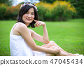 Young woman with a crown of flowers 47045434