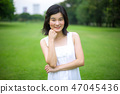 Young woman in green grass 47045436