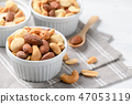 salted cocktail nuts on white wood 47053119