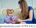 Young mother and her baby daughter looking photobook 47053421