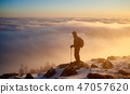 Tourist with backpack hiking on rocky mountain peak on background of foggy valley and blue sky at 47057620