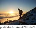 Tourist with backpack hiking on rocky mountain peak on background of foggy valley and blue sky at 47057621