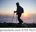 Tourist with backpack hiking on rocky mountain peak on background of foggy valley and blue sky at 47057623
