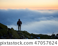 Tourist with backpack hiking on rocky mountain peak on background of foggy valley and blue sky at 47057624