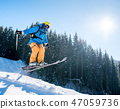 Professional skier jumping in the air while skiing in the mountains blue sky on the background 47059736