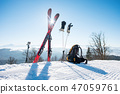 Shot of skiing equipment - skis, backpack, sticks, gloves and action camera on monopod, on top of 47059761