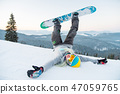 Excited young snowboarder woman having fun on the slope lying on the snow with her legs in the air 47059765