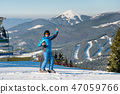 Full length shot of a smiling female skier showing thumbs up while skiing on the snowy slope at the 47059766