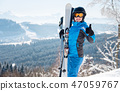 Happy female skier wearing blue ski suit, black helmet and mask smiling showing thumbs up posing in 47059767
