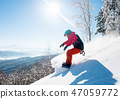 Shot of a freeride snowboarder riding in the mountains wearing snowboarding gear 47059772