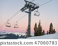 Ski lift chairs on winter resort against a beautiful sky at sunset 47060783