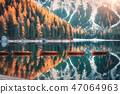 Wooden boats on Braies lake at sunrise in autumn 47064963