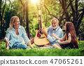 Happy family play guitar and sing together in park 47065261