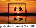 Couple young girls silhouette are sitting on swing 47076081