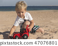 Caucasian child boy playing toy red tractor, excavator on a sandy beach at sunny day. 47076801