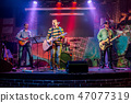 Band performs on stage in a nightclub 47077319