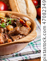 Beef Bourguignon stew served with baguette 47082349