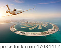 Private jet plane flying above Dubai city 47084412