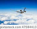 Passengers commercial airplane flying above clouds 47084413