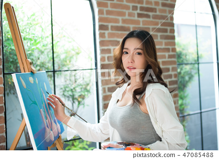 Beautiful young woman painting on a canvas finish 47085488