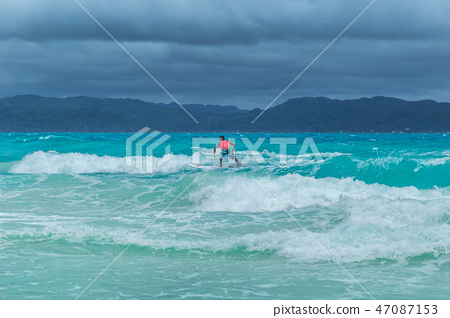 Surfer on turquoise azure Ocean Wave in Siargao, Philippines 47087153