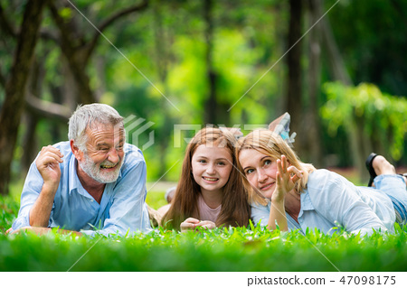 Happy family relaxing together in the park in summer. Concept of family bonding and relationship. 47098175