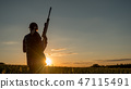 Sport shooting and hunting - woman with a rifle at sunset 47115491